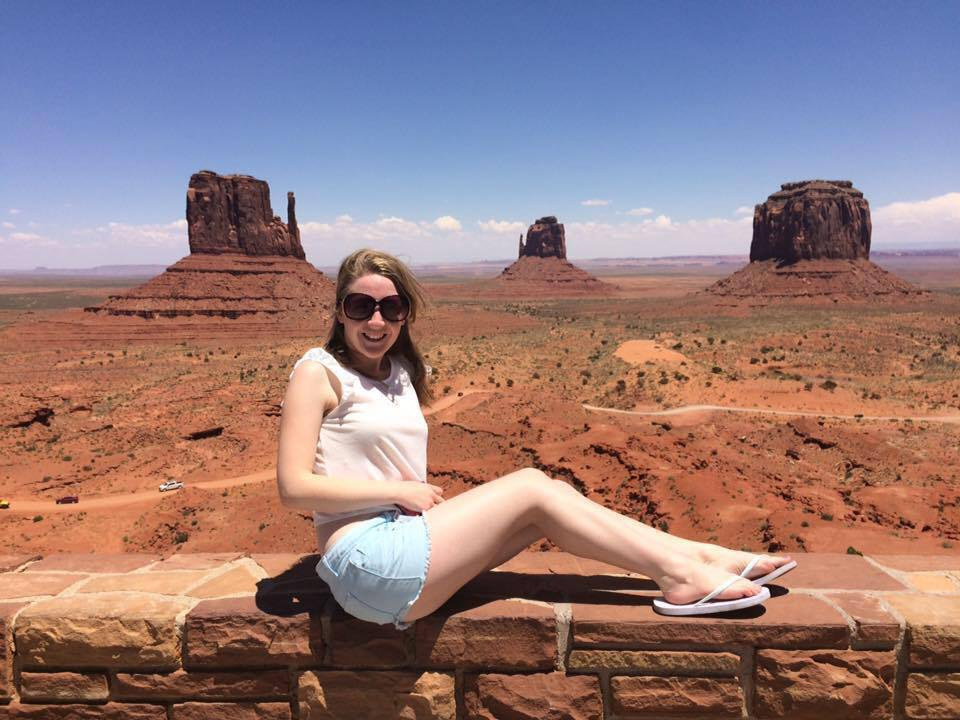 Jess Buck is sat on a wall with the backdrop of Monument Valley