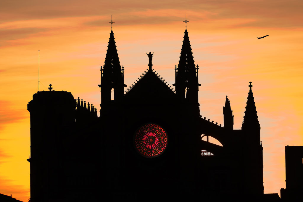 Cathedral in Palma, Mallorca at sunset illuminated by the orange sky.