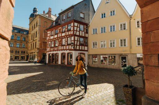 Mainz Junge Frau mit Fahrrad bewundert Mainzer Altstadt, Fachwerk im Hintergrund